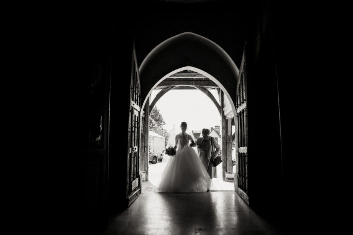la mariée entre dans l'église au bras de sa mamie