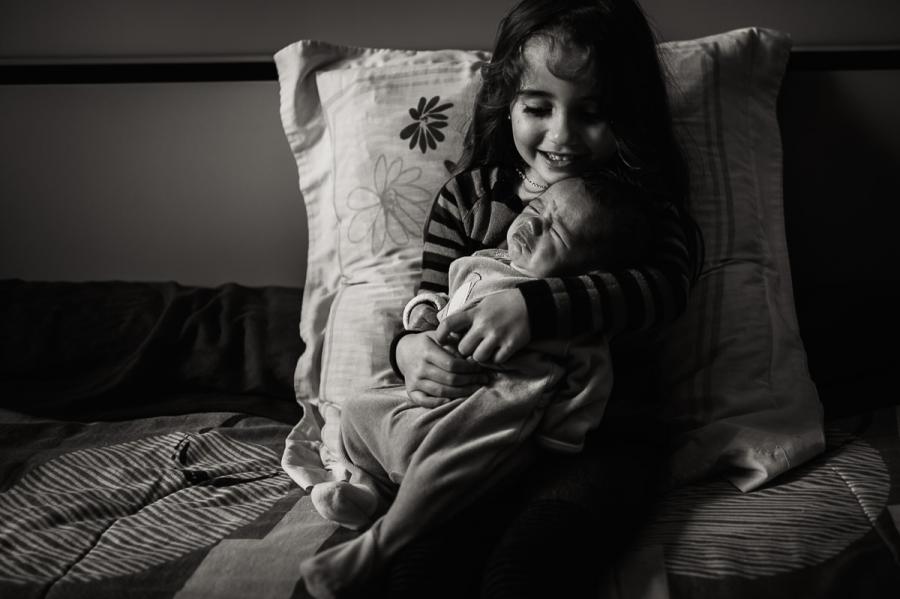 photo de bébé dans les bras de sa grande sœur - photographe maternité Eure et Loir